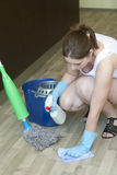 Young girl removing spot from the wooden floor Royalty Free Stock Photo