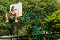 Young girl replacing a basketball net Stock Image