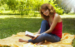 Young girl reposes in park with book Stock Image