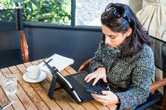 Young girl researching on tablet and smartphone. Young girl researching something on the internet with her tablet and phone, notebook and cappuccino aside on a royalty free stock image