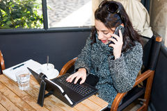 Young girl researching on tablet and talking on smartphone Royalty Free Stock Photography