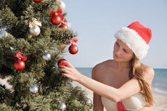 Young girl at the resort dreams about Christmas. Young girl at a resort in Santa hat dreaming about Christmas Stock Photography