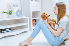 Young girl is resting with a dog on the floor at home . Royalty Free Stock Photos