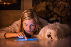 Young girl is resting with a dog at home . Young girl is resting with a dog at home and using tablet royalty free stock images