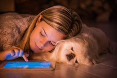 Young girl is resting with a dog at home . Young girl is resting with a dog at home and using tablet royalty free stock photo