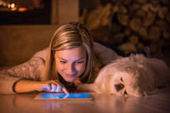 Young girl is resting with a dog at home . Young girl is resting with a dog at home and using tablet Stock Photo