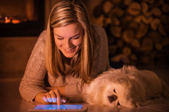 Young girl is resting with a dog at home . Young girl is resting with a dog at home and using tablet Royalty Free Stock Image