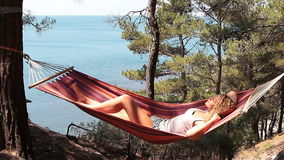 Young girl resting in a hammock stock video
