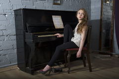 A young girl resting at the piano Royalty Free Stock Photos