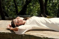 Young girl resting on the rocks. A portrait of a pretty teenage girl resting on a large rock out in nature Stock Photography