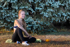 Young girl resting sitting on the grass. Girl is resting sitting on the grass in the summer park in the evening after fitness Royalty Free Stock Photography