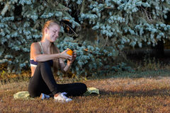 Young girl resting sitting on the grass. Girl is resting sitting on the grass in the summer park in the evening after fitness Stock Image