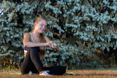 Young girl resting sitting on the grass. Girl is resting sitting on the grass in the summer park in the evening after fitness Royalty Free Stock Photos
