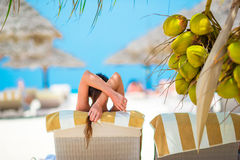 Young girl resting on sun lounger under a coconut tree Royalty Free Stock Images