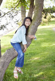 Young girl resting on a tree branch Royalty Free Stock Image