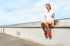 Young girl resting by wall. Jogging outfit. Royalty Free Stock Photos