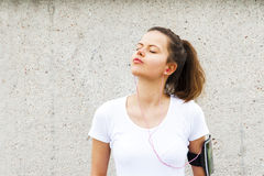 Young girl resting by wall. Joging outfit. Stock Images
