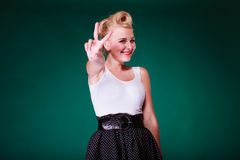 Young girl in retro dress showing peace sing. Signs, gestures concept. Lovely young pinup girl in retro black and white dress with big belt, showing peace sing Stock Photography