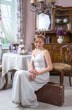 Young girl in a retro style wedding dress is sitting on a suitca Stock Photos