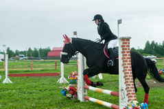 Young girl rider on a horse overcomes obstacles Stock Photos