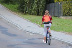 A young girl rides a bicycle on the road by the road sign of danger and speed limits of up to 40 km/h. Active way of life of young royalty free stock photos