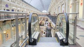 Young girl rides on the escalator stock video