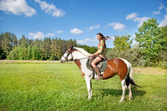 A young girl rides a paint horse. A young girl dressed as an Indian rides a paint horse royalty free stock photo