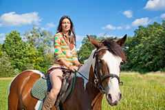 A young girl rides a paint horse Stock Photography