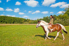 A young girl rides a paint horse. A young girl dressed as an Indian rides a paint horse Royalty Free Stock Photography
