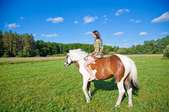 A young girl rides a paint horse Royalty Free Stock Photography