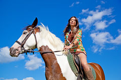 A young girl rides a paint horse. Stock Image