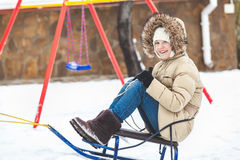 Young girl rides on sled in winter Royalty Free Stock Photo
