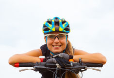 Young girl riding bicycle outside. Healthy Lifestyle. The young woman riding bicycle outside. Healthy Lifestyle. View against white sky royalty free stock image