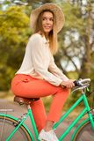 Young girl riding bicycle in park. And smiling Royalty Free Stock Photography