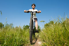 Young girl riding a bike. On a field path - offroad Stock Photo