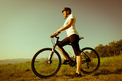 Young girl riding a bike. On a field path - offroad Stock Image