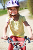 Young Girl Riding Bike Along Country Track Stock Photography