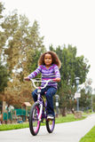 Young Girl Riding Bike In Park Stock Photo
