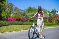 Young girl riding a bike on tropical resort Royalty Free Stock Photo