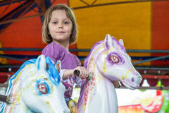 Young girl riding carousel horses Royalty Free Stock Image