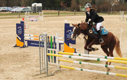 Woman on the horse at jumping competition. Young girl  riding her horse at a jumping competition Stock Photo