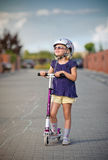 Young girl riding her scooter Stock Image