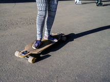 Young girl riding on a longboard in city Royalty Free Stock Photo