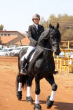 Young girl riding lovely black Friesian horse. Royalty Free Stock Photo