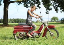 Young girl riding a motorbike Royalty Free Stock Image