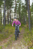 Young girl riding a mtb. Young girl going along a trail Stock Photography