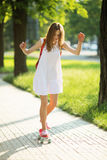 Young girl riding in the park on a skateboard Royalty Free Stock Photography