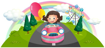 A young girl riding in a pink car with balloons Stock Image