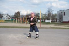 Young girl riding on roller skates. Little girl learning to roller skate Royalty Free Stock Photo