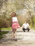 Young girl riding scooter away from camera to father in park Stock Photos